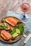Le casse-croûte avec les poissons et l'avocat rouges a servi d'un plat en bois, champagne rose dans un verre, fourchette de cuill Photographie stock libre de droits