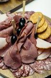 Le casse-croûte d'antipasti de plat de viande avec du jambon de Prosciutto, le pain, les saucisses, les pepperoni et les olives s image stock