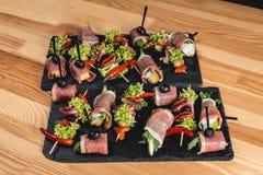 Le casse-croûte espagnol, banderillas sur des brochettes avec le jamon, ramses, poire, dorblue, chorizo, a séché la tomate, champ Image stock