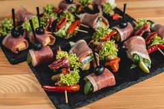 Le casse-croûte espagnol, banderillas sur des brochettes avec le jamon, ramses, poire, dorblue, chorizo, a séché la tomate, champ Photos libres de droits