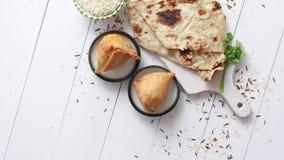 Le casse-croûte indien traditionnel Samosa de nourriture a servi dans un plat sur une table en bois blanche banque de vidéos