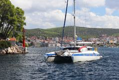 Le catamaran de navigation navigue le long de la côte verte rocheuse après le signe littéraire rouge - le phare de fairway Ville  image libre de droits