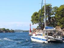 Le catamaran de navigation navigue le long de la côte verte rocheuse après le signe littéraire rouge - le phare de fairway Ville  image stock
