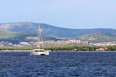 Le catamaran de navigation navigue le long de la côte verte rocheuse après le signe littéraire rouge - le phare de fairway Ville  photos stock