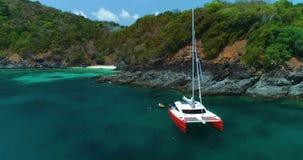 Le catamaran orange lumineux de yacht se tient dans la lagune à côté de la plage blanche de sable banque de vidéos