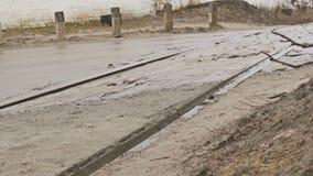 Le cattive automobili della strada asfaltata guidano sull'autunno della pioggia dei pozzi della sporcizia stock footage