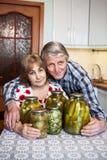 Le Caucasien de sourire a vieilli des couples se reposant dans la cuisine domestique avec les boîtes en verre avec le pickler Photo stock