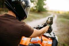 Le cavalier d'Atv ajuste le rétroviseur avant voyage photos stock