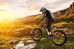 Le cavalier dans le plein équipement de protection sur le vélo de mtb monte vers le coucher du soleil dans les rayons du soleil d Images stock