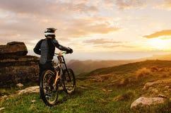 Le cavalier dans le plein équipement de protection sur le vélo de mtb monte vers le coucher du soleil dans les rayons du soleil d Photo libre de droits