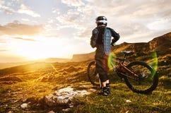 Le cavalier dans le plein équipement de protection sur le vélo de mtb monte vers le coucher du soleil dans les rayons du soleil d Photos libres de droits