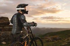 Le cavalier dans le plein équipement de protection sur le vélo de mtb monte vers le coucher du soleil dans les rayons du soleil d Images libres de droits