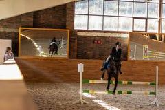 Le cavalier de fille sur l'étalon de baie surmonte la barrière sous t photo stock