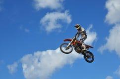 Le cavalier de MX sur la motocyclette décolle de la colline Image stock