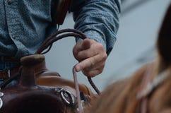 Le cavalier se tient sur des rênes de son cheval Photographie stock libre de droits