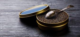 Le caviar noir peut dedans et cuillère images stock