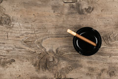 Le cendrier en verre avec le cigare se tient sur une surface en bois Photographie stock