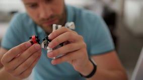 Le centre sélectif du mâle remet le robot de bâtiment dans le studio banque de vidéos