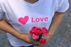 Le centre sélectif et la profondeur du champ d'un beau bouquet des roses rouges est tenu en main de la femme âgée par milieu avec Images stock