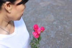 Le centre sélectif et la profondeur du champ d'un beau bouquet des roses rouges est tenu par la femme avec le fond blanc de chemi Photographie stock libre de droits