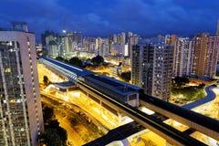 Le centre ville et train à grande vitesse urbains de Hong Kong la nuit Photographie stock