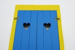 Le châssis de fenêtre jaune et la porte en bois bleue avec deux lacunes creuses de forme de coeur d'une maison affrontent en île  Image stock