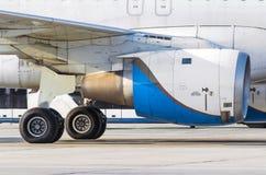 Le châssis et le moteur des avions sur la piste de roulement à l'aéroport Images libres de droits