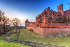 Le château de l'ordre Teutonic dans Malbork au coucher du soleil Image stock