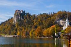 Le château et l'église au-dessus du lac ont saigné en automne Images stock