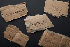 Le chômage, problèmes, effort, aide, le travail Inscriptions sur le carton photos libres de droits