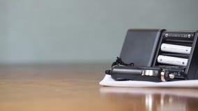 Le chager de batterie s'étendent sur la feuille blanche, sur la table en bois Photo libre de droits