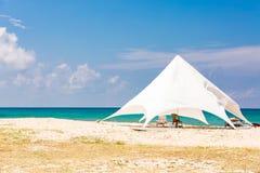 Le chaise-lounge del sole nell'ambito di grande parasole sulla spiaggia idilliaca Tenda bianca sulla spiaggia Fotografia Stock Libera da Diritti