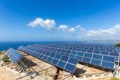 Le champ des panneaux solaires s'approchent de la mer Images stock