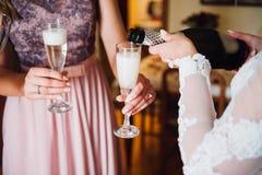 Le champagne de boissons de jeune mariée et d'amie Fin-upr Photographie stock