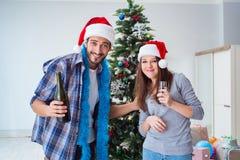 Le champagne potable heureux d'ami et d'amie sur Noël Images libres de droits