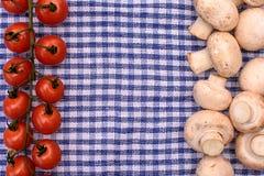 Le champignon de paris de champignons de blanc et les tomates-cerises rouges se trouvent sur une serviette bleue, l'espace pour l Images stock