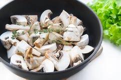 Le champignon de paris rôti répand avec la branche de thym dans la casserole sur la table en bois blanche Images libres de droits