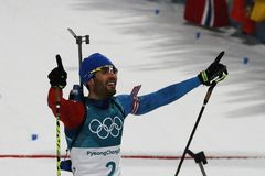 Le champion olympique Martin Fourcade des Frances célèbre la victoire dans le début de masse du ` s 15km d'hommes de biathlon aux Image libre de droits