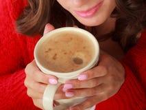 Le chandail rouge de fille tient la tasse avec du café Photographie stock libre de droits