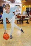 Le chandail s'usant de jeune homme projette la bille dans le bowling Image libre de droits
