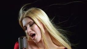 Le chanteur exécute des chansons dans un rétro microphone Fond noir Fin vers le haut banque de vidéos