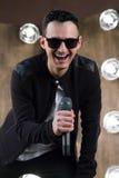 Le chanteur masculin dans des lunettes de soleil avec le microphone chante en Li de projecteurs Photos libres de droits