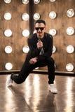 Le chanteur masculin dans des lunettes de soleil chante sur la scène dans des lumières de projecteurs Photographie stock libre de droits