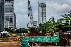 Le chantier de construction avec des matériaux et les équipements s'approchent du bâtiment ayant beaucoup d'étages Jakarta rentré Photo libre de droits