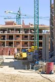 Le chantier espagnol type avec la moitié a construit la propriété et la grue Photographie stock
