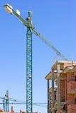Le chantier espagnol type avec la moitié a construit la propriété et la grue photos stock