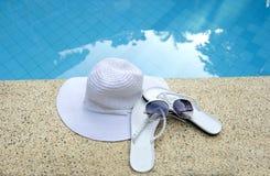 Le chapeau blanc chausse l'eau bleue de regroupement de lunettes de soleil Images stock