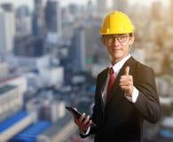 Le chapeau d'ingénieur d'homme d'affaires font le signal par le pouce sur le backg de ville de tache floue Photos libres de droits