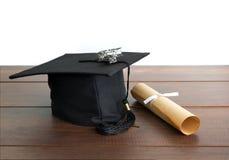 le chapeau d'obtention du diplôme, le chapeau avec le papier de degré et l'avion jouent sur le tabl en bois Images stock