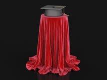 Le chapeau d'obtention du diplôme sur la table a couvert le tissu Image stock